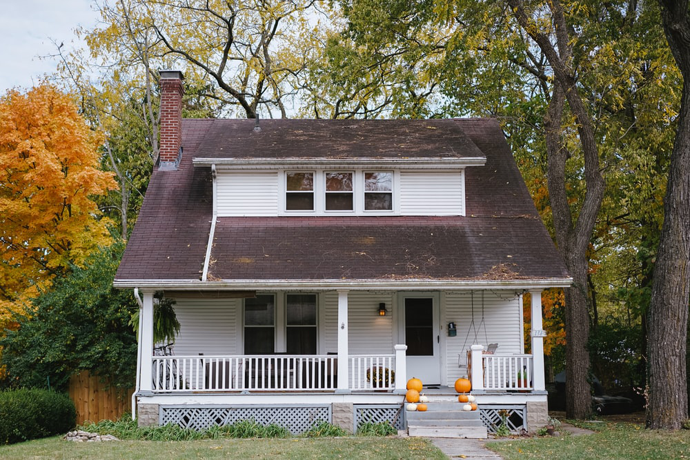 A house with a white picket fence and a grey roof, surrounded by trees