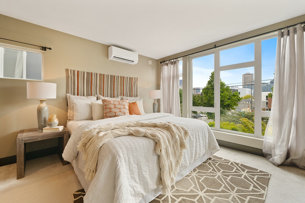 A photo of a luxury bedroom with a master bed and wall-length windows