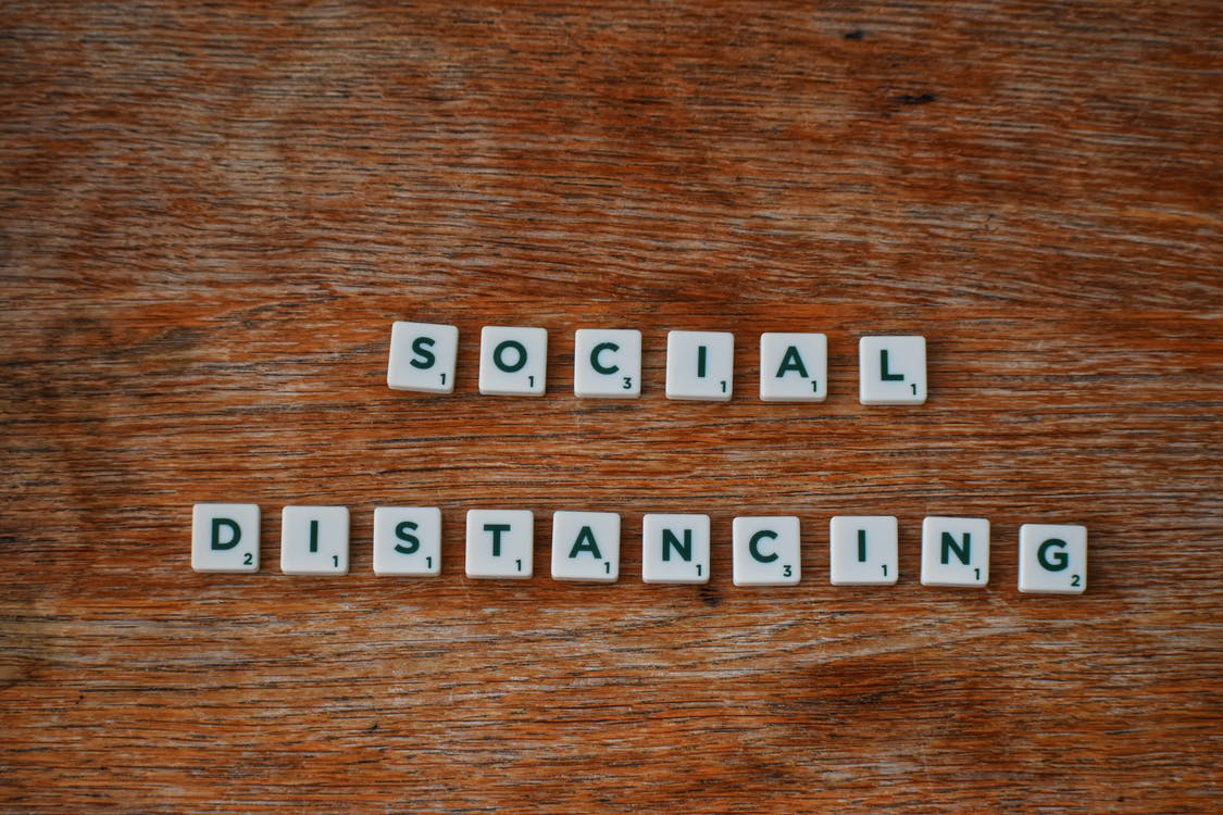 "A wooden surface with Scrabble letters that form the words ""Social Distancing"" on them."