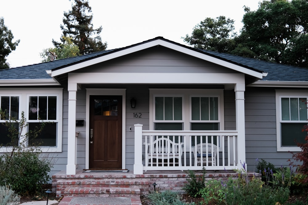 A simple white and grey single-story wooden house